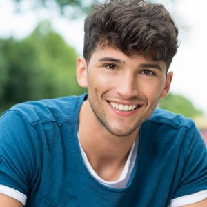 Image of a happy young man who was able to maintain a beautiful smile with routine dental cleanings done at a dental clinic in Lincoln, NE.